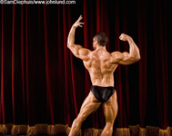 Image of a champion bodybuilder in a classic bodybuilding pose showing off his well developed back muscles to the audience and the judges of the competition. His arms are up as he flexes his arm shoulder and back muscles.